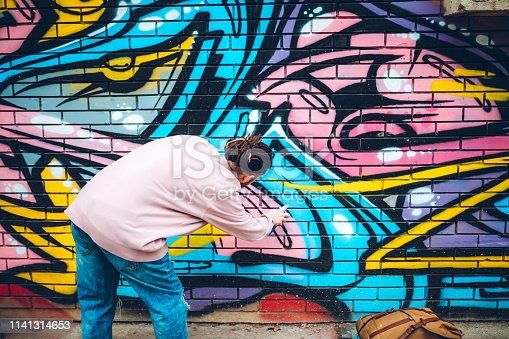Young man with dreadlocks is painting graffiti with spray paint