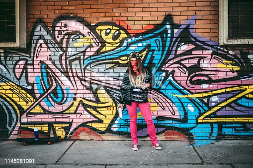 Young woman with bandana is holding aerosol can of spray paint