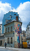 Paris-France, April 25, 2018; Young man walking in front of colorful graffiti in Paris