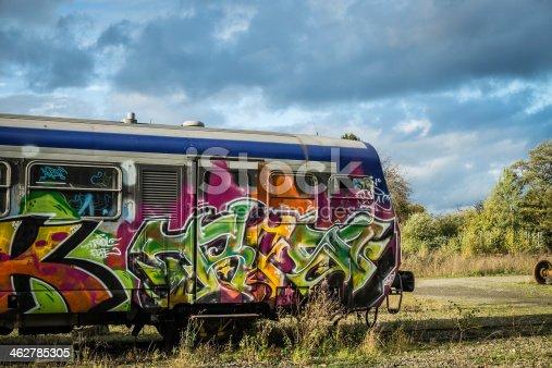 Graffiti on an abandoned train below a dramatic sky