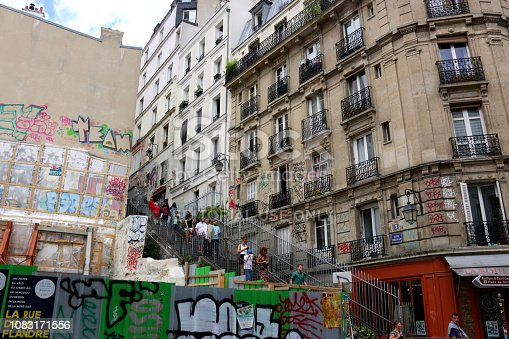 Paris, France- July 7, 2015: people walking up and down stairs by buildings that have classic french architecture and grafitti in montmartre in paris, france in the summer of 2015