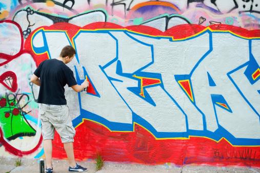 Grafitti artist in action, Berlin Wall