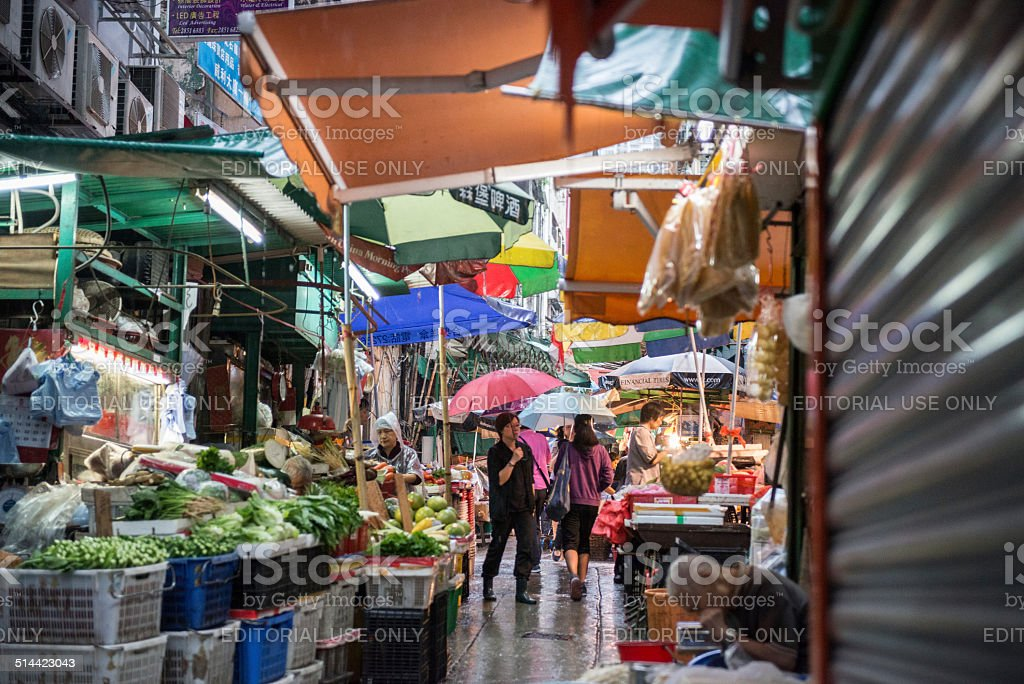 Shoppers and shopkeepers try to keep dry during a downpour at the...