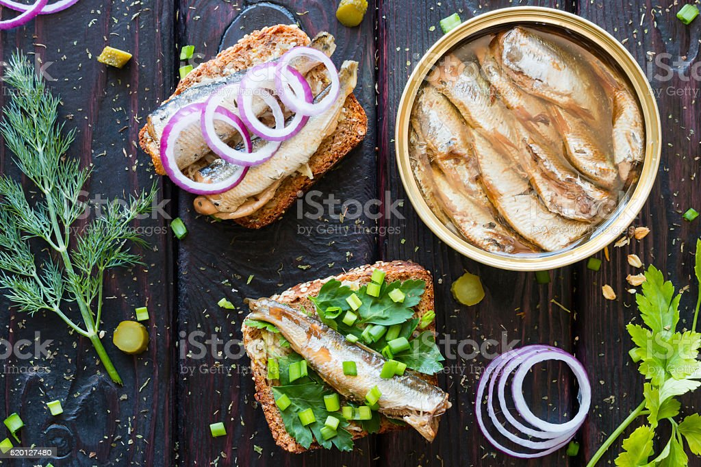 grain bread with sardines and greens next to the bank stock photo