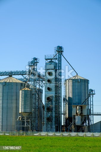 Grain elevator silos. Agriculture factory. Storage tanks agricultural crops processing plant.