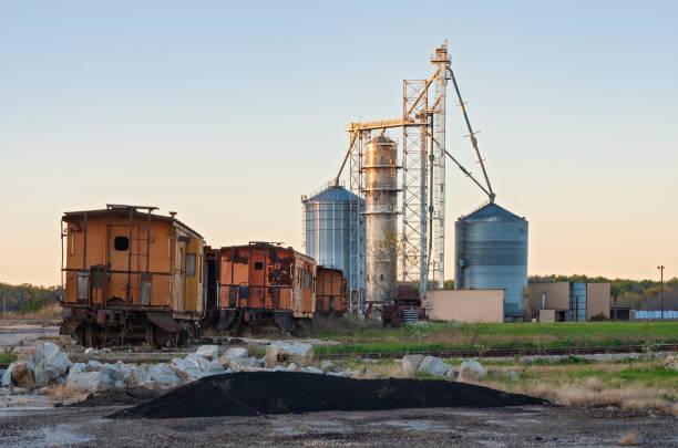 Grain Elevators and Rusty Abandoned Railcars stock photo