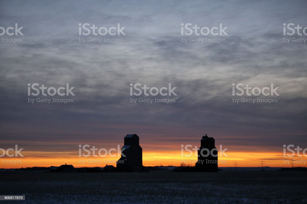 Grain elevators silhouetted against a sunset stock photo
