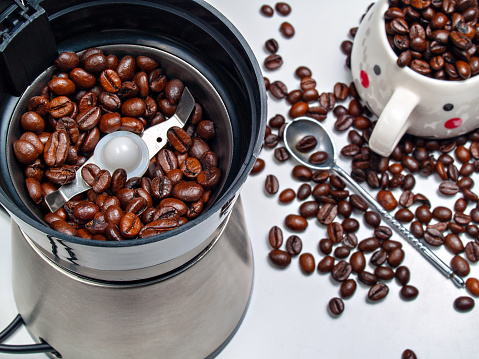 Grains of coffee in an electric coffee grinder, scattered grains on the table, a spoon and a cup of coffee beans