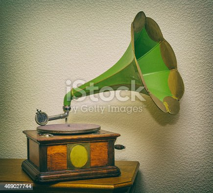 old wooden mechanical gramophone with a copper pipe to play vinyl records, interior, photo in old style image.