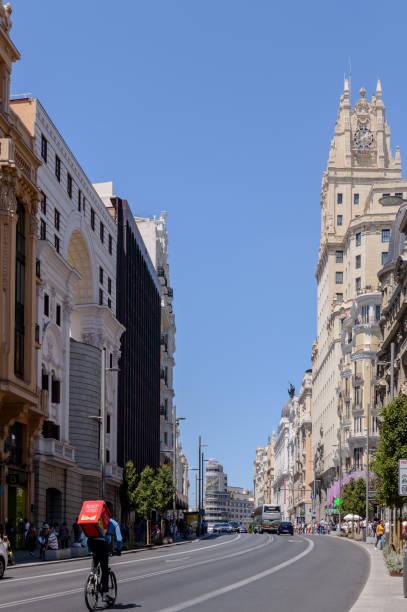 Gran Via praktisch verlassen nur ein Haus Lieferung Food Bike In Madrid. – Foto