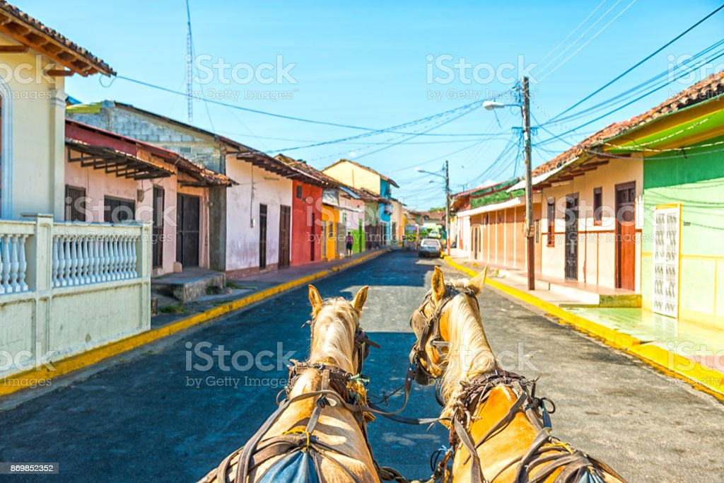 Granada by horse carriage Site seeing by horse carriage the old city Granada in Nicaragua. Colorful facades against blue sky. Animal Stock Photo