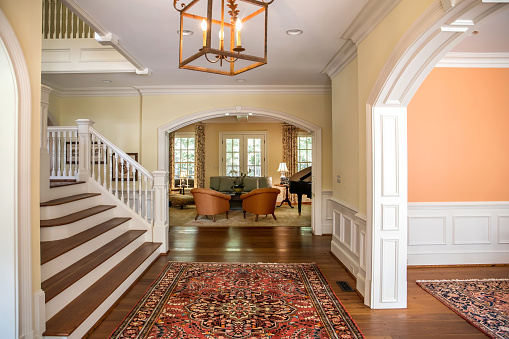 Grand and elegant yellow entrance to a home with stairs. Oriental rug and wood and glass door
