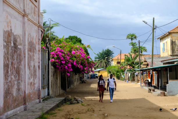 Grand Bassam young couple Grand Bassam, Cote D'Ivoire – April 9 2018: Young couple stroll through bougainvillea lined street in old colonial district of former capital of Ivory Coast côte d'ivoire stock pictures, royalty-free photos & images