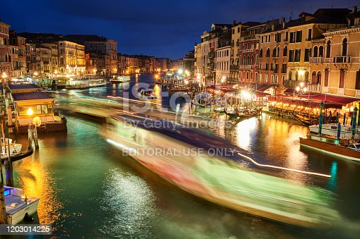 Venice, Italy - November 23, 2019: Night view of gondolas and passenger ships sailing on Grand Canal. On the sides of the canal people dining in local restaurants.