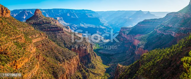 Panoramic vista down the Bright Angel Trail to the green oasis of Indian Garden and the early morning rays of sunlight illuminating the North Rim of the Grand Canyon National Park, Arizona, USA.