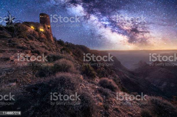 Photo of grand canyon desert view watchtower at night with milky way