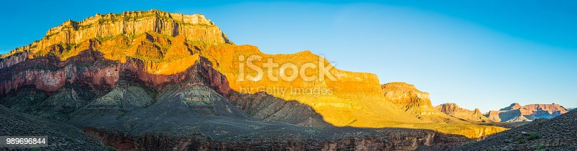 The vibrant desert walls of the South Rim illuminated by the warm light of sunrise from the remote Tonto Trail deep in the Grand Canyon National Park, Arizona, USA.