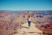 Panoramic view of Grand Canyon national park in Arizona, USA. Woman is standing on steep cliffs enjoying the beautiful view. Freedom concept
