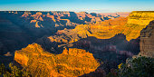 Warm light of sunset illuminating the iconic rocky buttes and mesas of the central Grand Canyon, Arizona, USA.