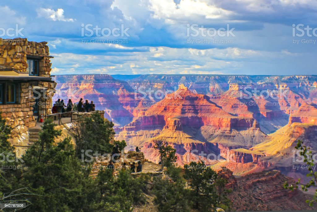 Grand Canyon South Rim view  at golden hour under stormy sky with tourists at lookout point taking pictures and selfies royalty-free stock photo