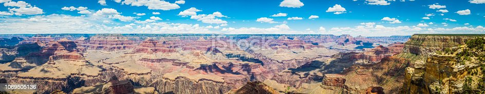 Panoramic view from the South Rim below little fluffy clouds over the iconic strata, mesas and ravines of the Grand Canyon National Park, Arizona, USA.