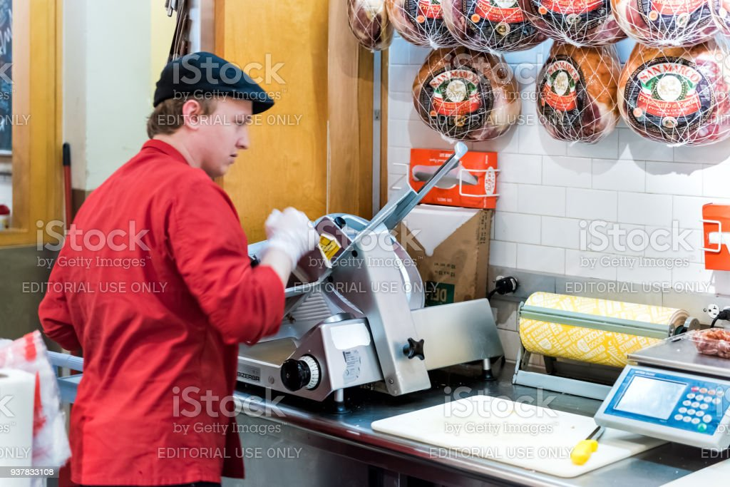 Grand Central Market in New York City with signs, Italian deli store shop, meat cuts, young butcher slicing ham machine closeup stock photo