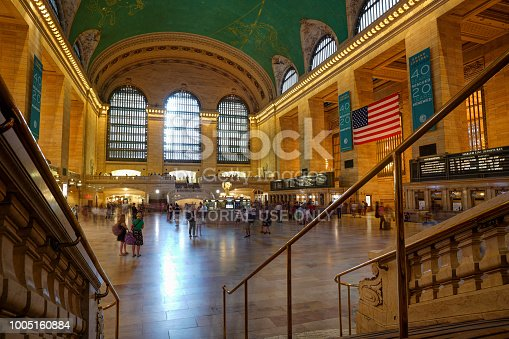 New York, USA - July 20, 2018: Interior view of the main concourse at historic Grand Central Terminal. Commuters leave blurred trails as they move around.