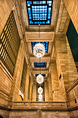 istock Grand central terminal entrance from subway in New York City with arched pathway corridor, nobody, looking up at ceiling with tiles, illuminated bright chandelier architecture 937833612