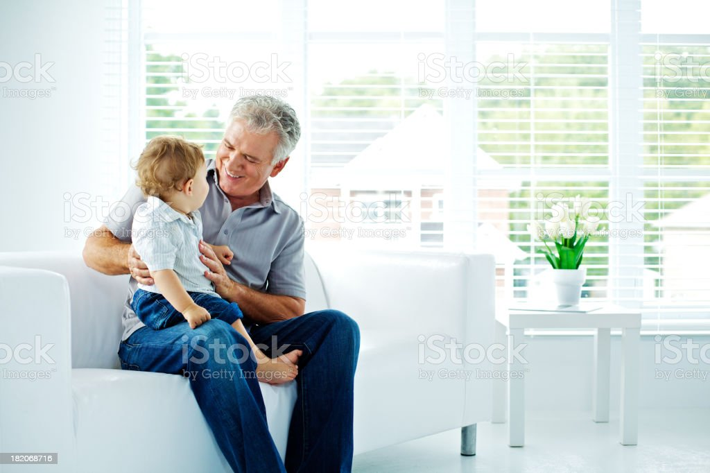 Grand father and little son having fun on a couch stock photo