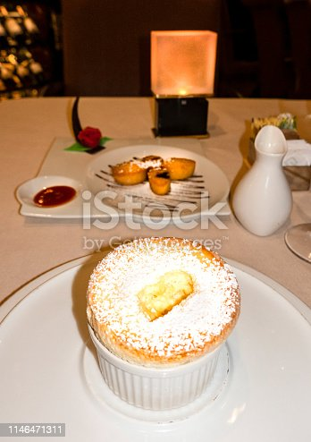 Grand Marnier soufflé  on table with candle.