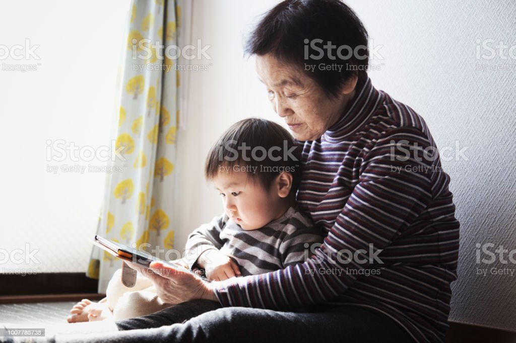 Grand mother and grand son using a digital tablet together royalty-free stock photo