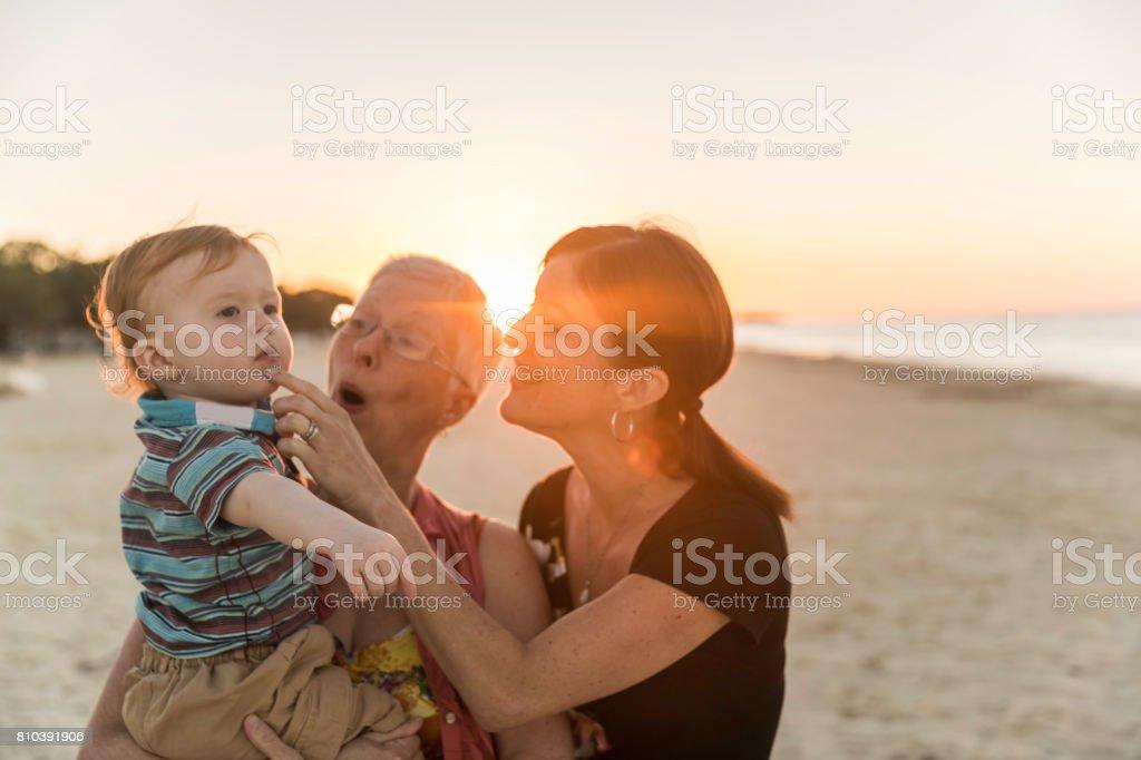 Gran madre y mamá con bebé en Sunset Beach - foto de stock