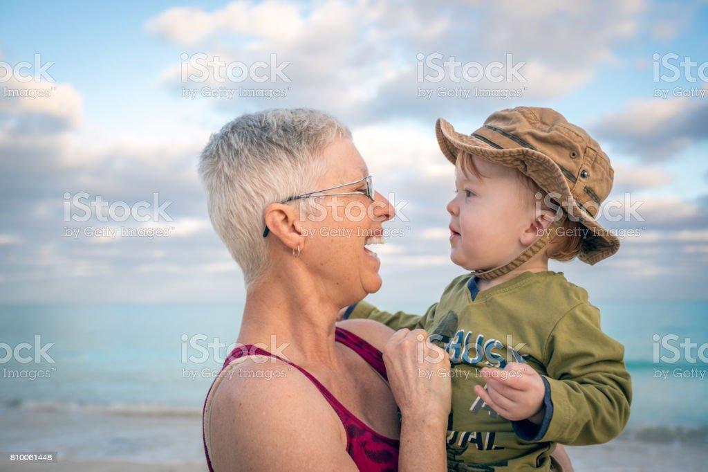 Gran madre Holding Baby Boy al atardecer de la playa - foto de stock