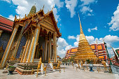 'Prasat Phra Thep Bidon in Grand Palace and Wat Phra Kaew Temple interior, Bangkok, Thailand. The Emerald Buddha temple. Visible are two of the many Buddha temple and the Golden Pagoda in interior of Grand Palace. Dramatic cloudscape with blue sky and cumulus clouds over the Grand Palace.See more images like this in:'