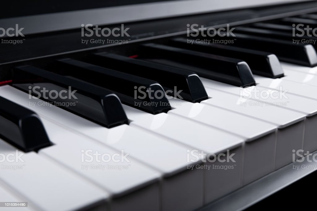 Grand piano keyboard with glossy black and white keys as a music,...