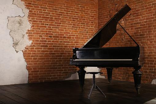 Grand piano with raised lid near brick wall