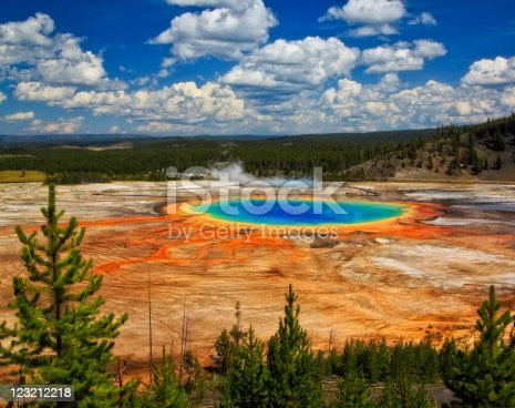 A wide-angle view of Grand Prismatic Spring with puffy clouds overhead in Yellowstone National Park, Wyoming.
