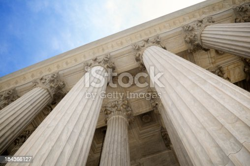 Grand classical stone columns soar up to decorative entablature at the Supreme Court building
