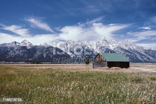 An abandoned house with a view of the Grand Teton mountain range from the Antelope Flats Rd, Moose, WY, USA.