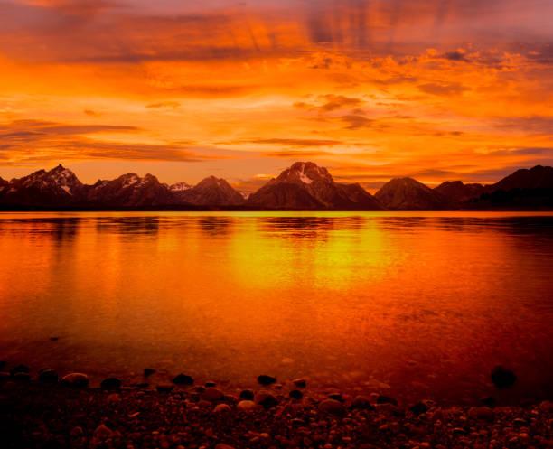 Grand Tetons Range  and orange sunset at Jackson Lake, WY stock photo