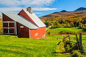 Stowe, Vermont, USA-October 17, 2017-A red barn with a backdrop of colorful autumn foliage on an unpaved road near Stowe, Vermont.