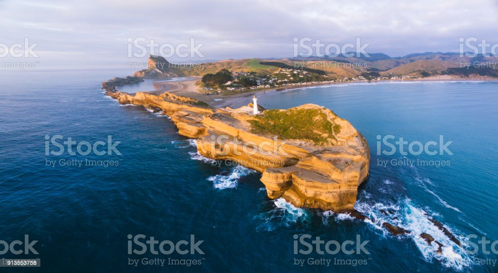 Grand view of Castlepoint Lighthouse with sunlight hitting shore. stock photo