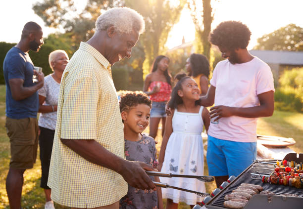 Grandad and grandson grilling at a family barbecue Grandad and grandson grilling at a family barbecue family bbq stock pictures, royalty-free photos & images