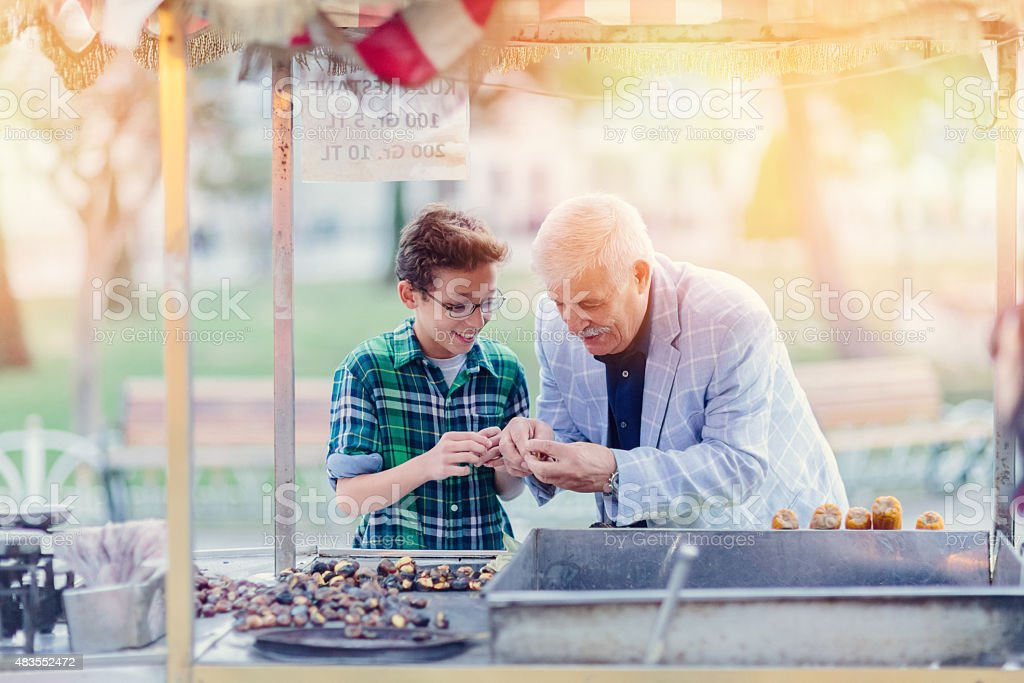 Grandafther and grandson buying roasted chestnuts stock photo