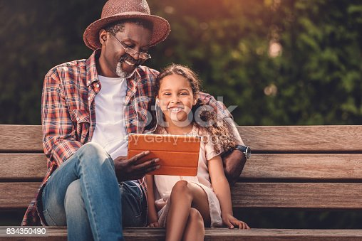 smiling african american grandchild and her grandfather listening music on digital tablet while sitting on bench in park