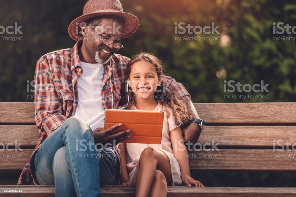 grandchild and her grandfather listening music on digital tablet stock photo