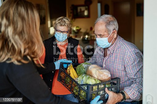 Senior couple on their 70s wearing a protective face mask picking up the groceries box that granddaughter is delivering in times of COVID-19, she is wearing mask and gloves.