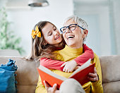 istock grandchild granddaughter grandma grandmother reading book girl senior 1202320335