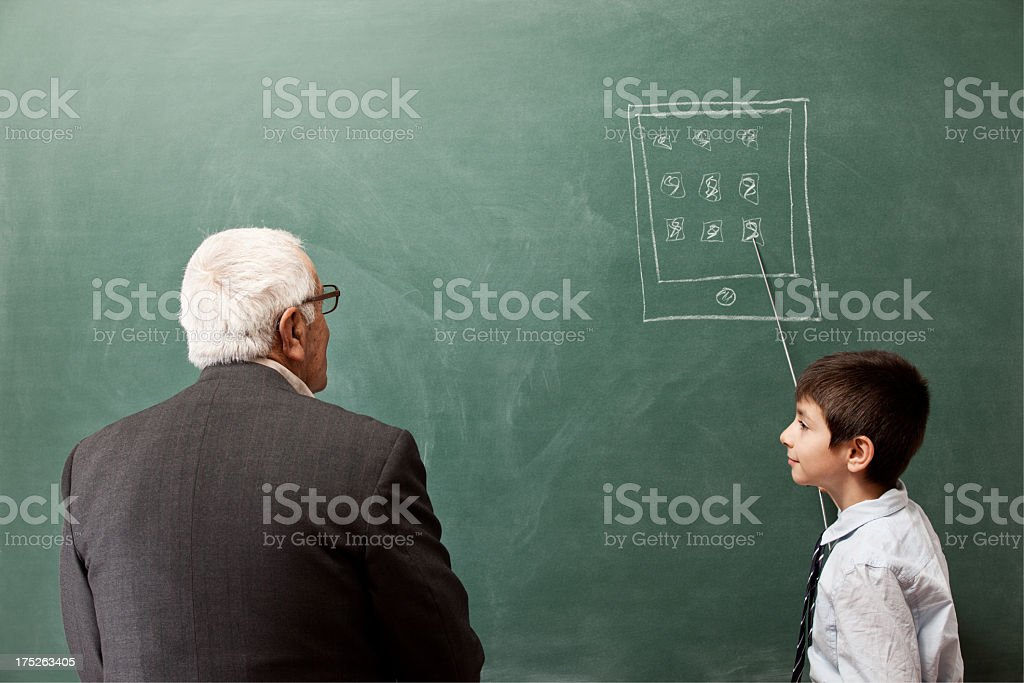 Grandchild teaching grandfather how to use smart phones on blackboard stock photo