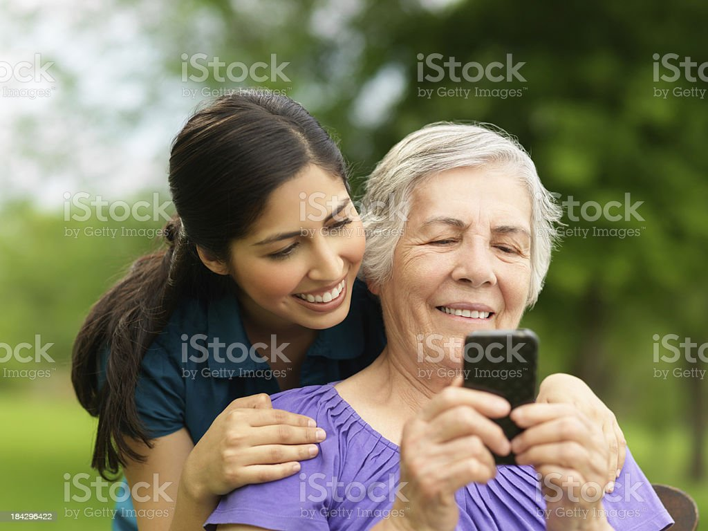 Grandchild teaching her grandmother how to use the cellphone royalty-free stock photo